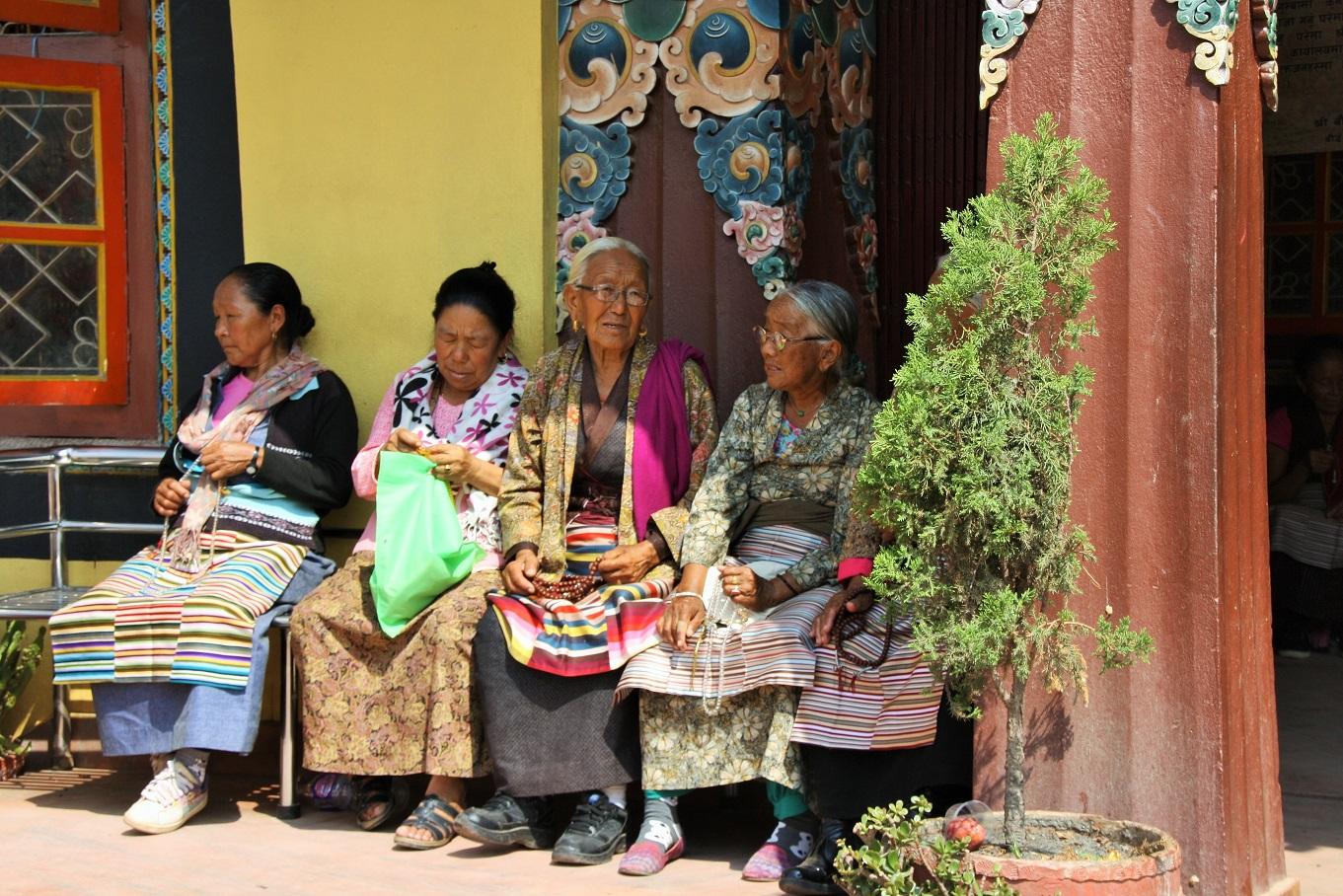 Nepalese vrouwen zitten voor een Tibetaans klooster