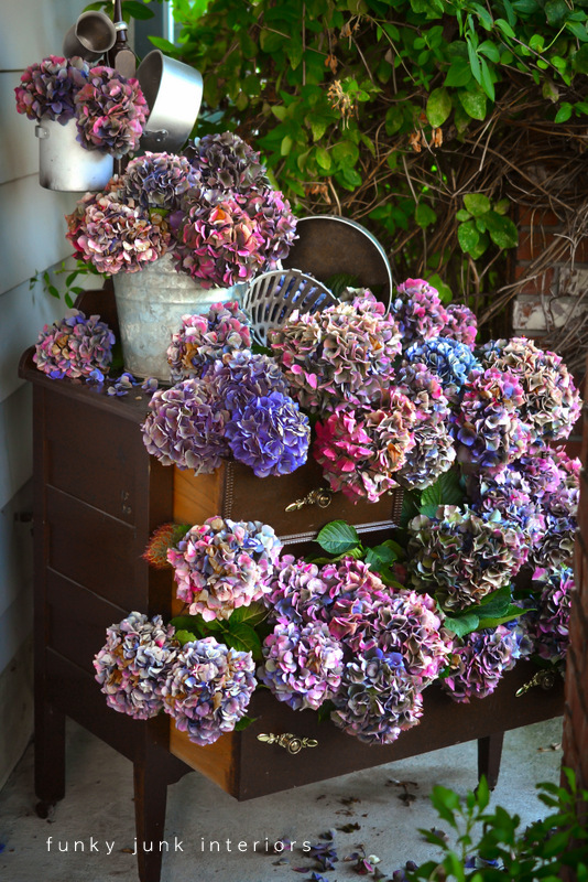 Multi coloured dried hydrangeas in a dresser outdoors via Funky Junk Interiors