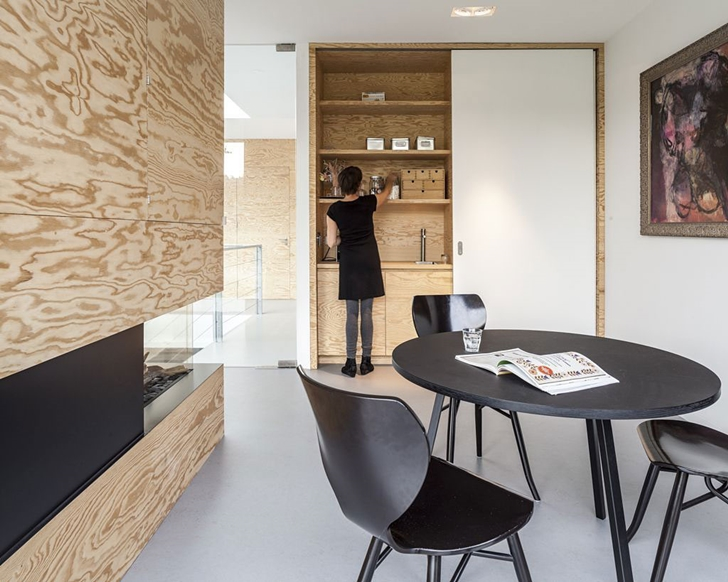 Black dining table in Modern Villa V by Paul de Ruiter Architects
