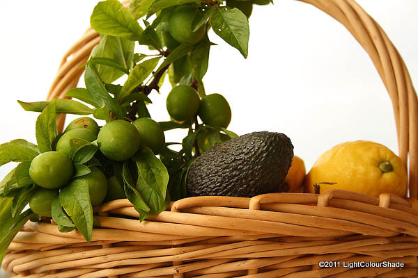 Sour plum twig, organic avocado and lemon in wicket basket