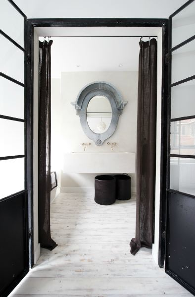 Bathroom with painted white wood floors, glass interior doors, dark sheer curtains, a metal mirror, and a large basin porcelain sink