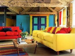 Żółta sofa, czerwona sofa, turkusowa ściana i kolorowy chodnik