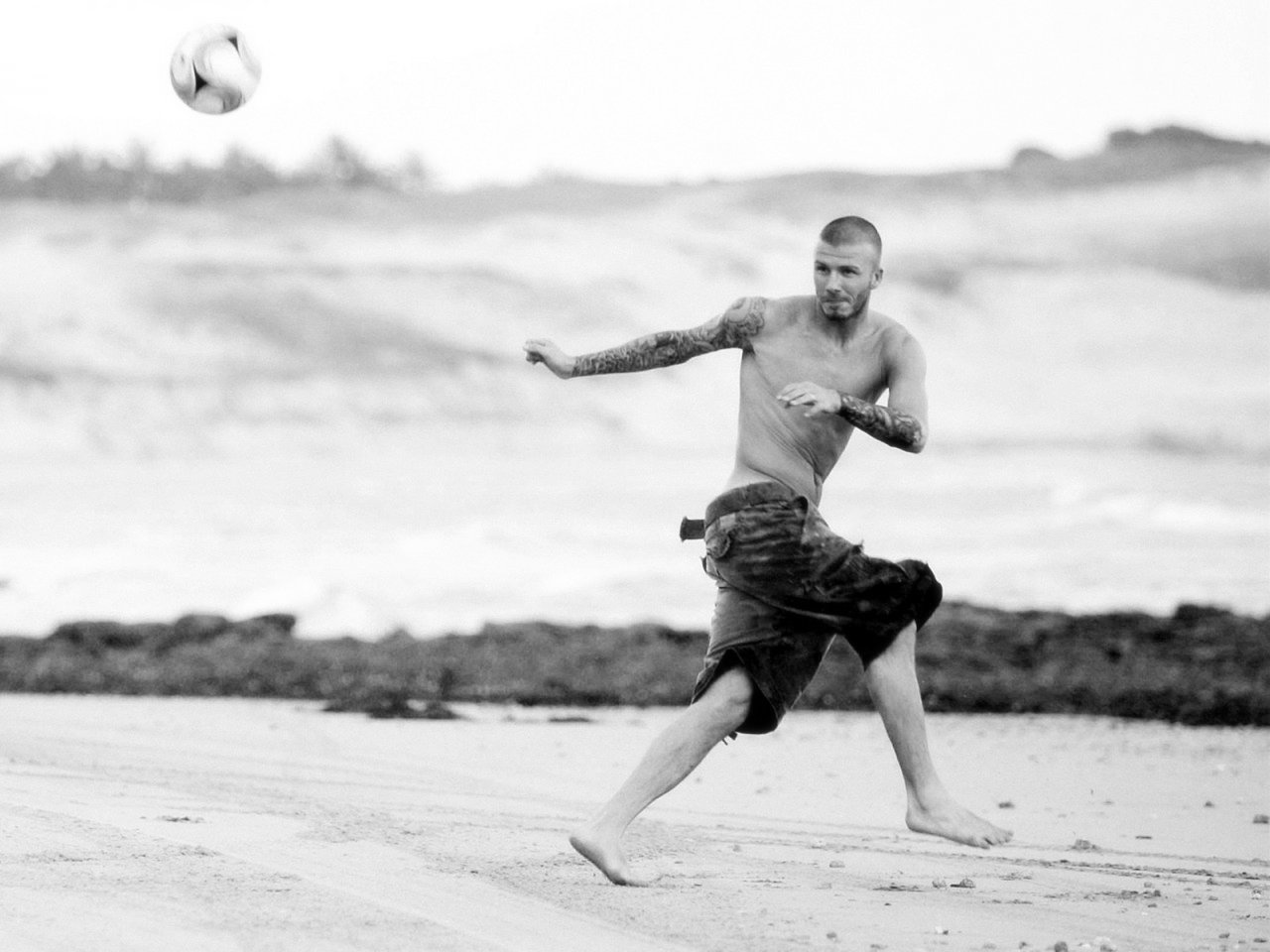 David Beckham playing on beach black and white Photography