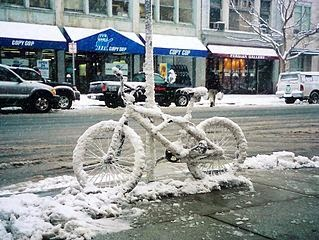 A bicycle completely iced over and frozen.