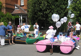 One green and one pink themed raft on the pavement waiting for their turn to launch