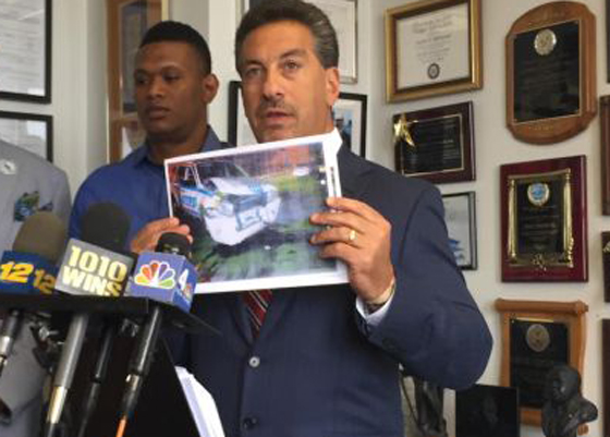 Oliver Wiggin's (left) attorney, Scott Rynecki, shows a photo of the smashed police car to the media. Wiggins was framed for DUI because the NYPD was trying to cover up for a cop who was driving a patrol car while drunk.