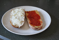 Vegetable demi-baguette, split and spread with goat cheese and tomato paste