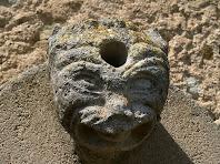 Cap de monstre, re-aprofitat, en la vessant de llevant de l'església de Sant Andreu de Gurb