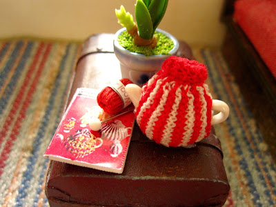 Modern dolls' house miniature trunk coffee table with a knitted tea cosy, knitting pattern, wool and a knitting needle on top.