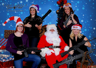 Santa Claus holding a gun with five other woman also holding guns