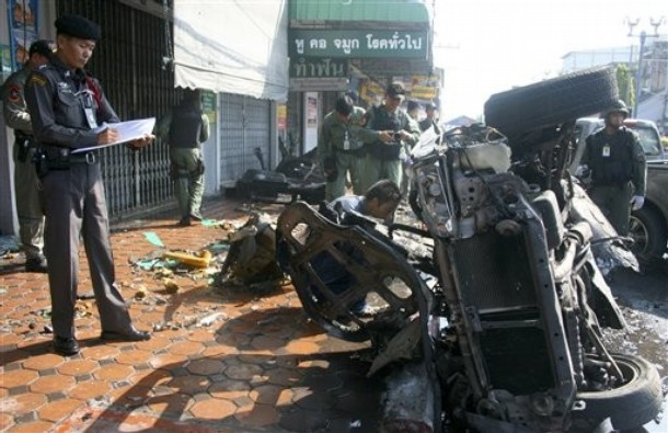 Thai police officers examine the site where a bomb exploded in Yala province Thailand on Monday April 2011