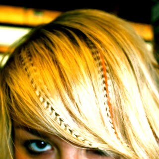 Trend feather hair extensions in blonde hair.