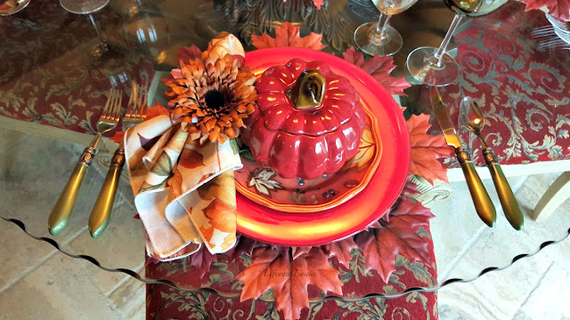 red pumpkin soup tureen with leaves salad plate and napkin ring