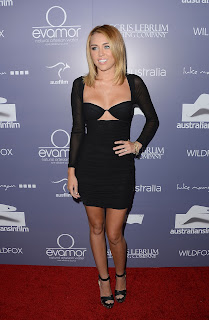 Miley Cyrus AIF strikes a pose in a revealing black outfit on the red carpet
