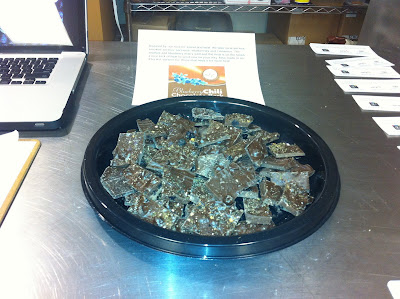 Round black place piled high with pieces of blueberry chili flavored chocolate bark.