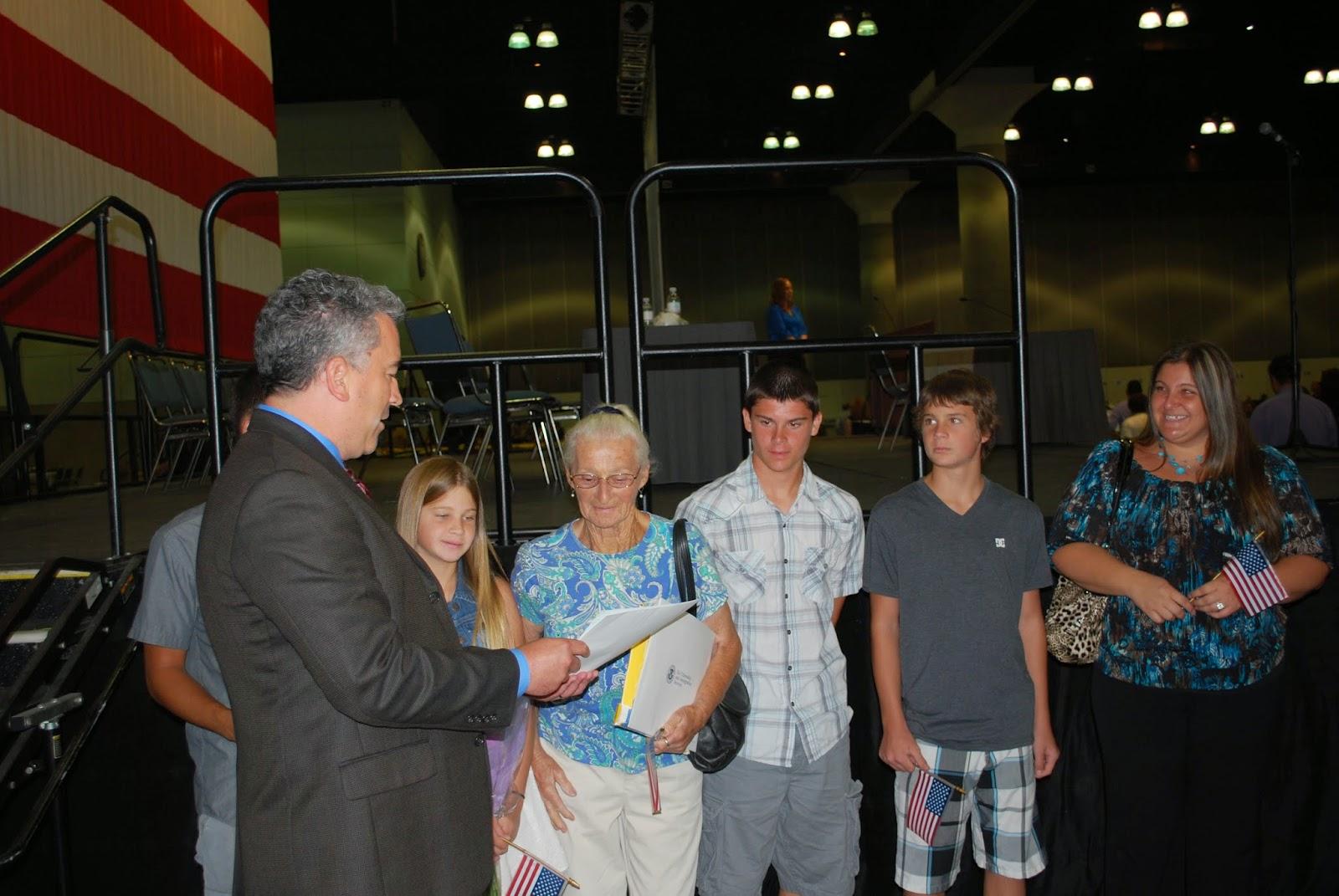 El director de la Oficina Local de USCIS en San Fernando Valley, Roland Lyons, le entrega a Helga Basses su Certificado de Ciudanía.