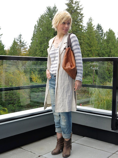 styling boyfriend jeans with a striped henley top, sleeveless coat, and ankle boots
