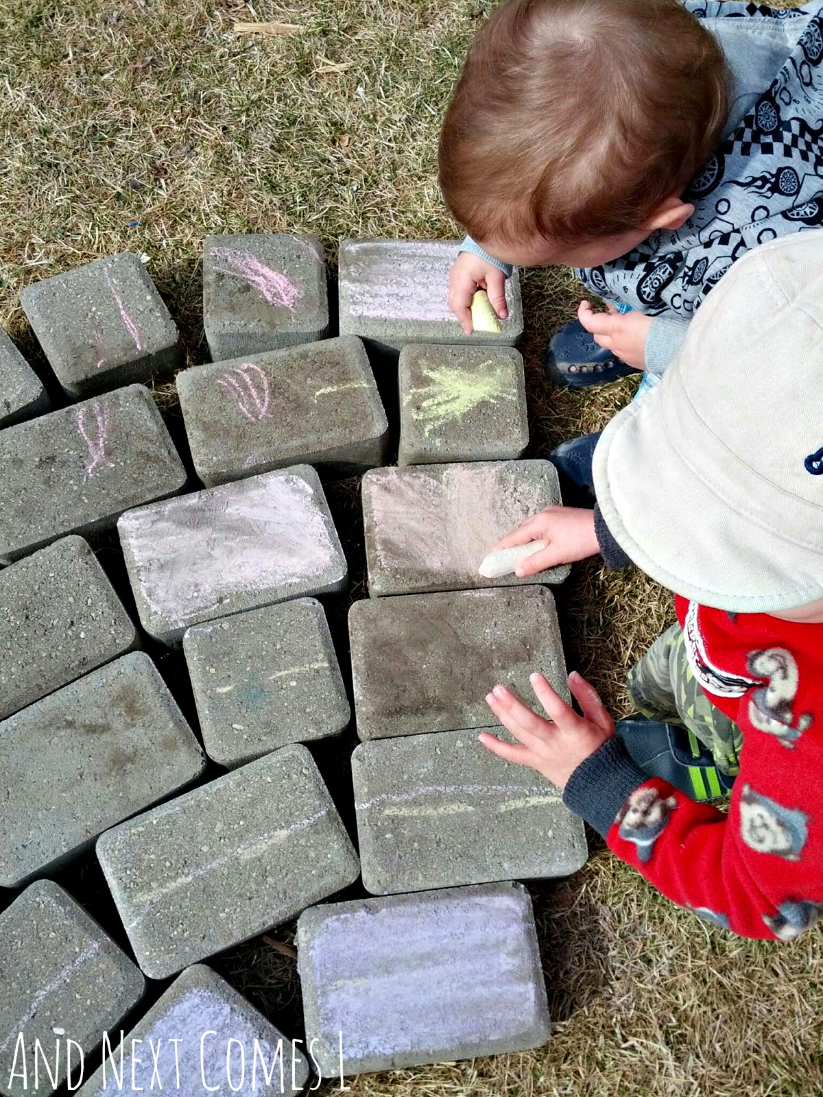 Brothers coloring paving stones with chalk to make a giant chalk rainbow from And Next Comes L