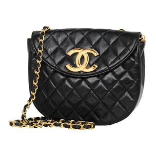 "Vintage 1990's black quilted leather Chanel bag with large gold ""CC"" logo and gold chain strap."