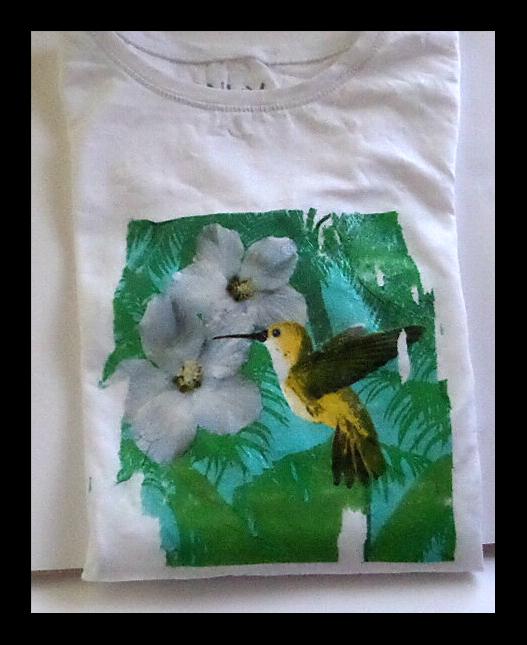 """<img alt="""" decoupage de motivos de colibrí y flor, en tonos verdes blancos y amarillos en camiseta """""""