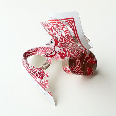 A red backed playing card which has been folded and cut into an abstract construction and held together with brown tape.