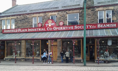 A colour photo of the relocated Annfield Plain co-op store at Beamish, a two story stone building with a four plate glass windows and three entrances, clothing, food and hardware.  A glass canopy ties the shop fronts together and the road in front is cobbled with inlaid tracks for the trams.