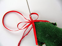 Sewing a bow to a felt Christmas Tree decoration