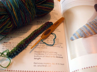 multicolor ball of yarn laying on a pattern book, with a swatch of extended single crochet laying in the front next to a crochet hook