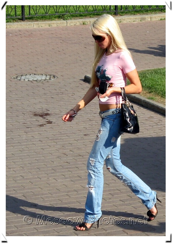 Blonde slim girl in stylish jeans and rose shirt