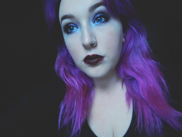 Girl with long purple hair wearing dark lipstick and dark eye makeup