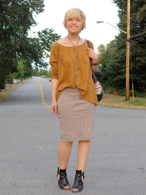 styling a striped pencil skirt with a distressed, long-sleeved tee, cut-out booties, and a Fossil bag