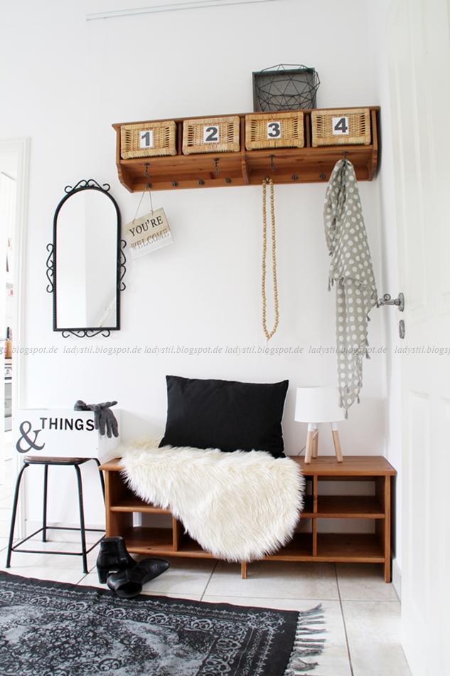 schwarz weiß Styling im Flur mit Holzgarderobe und Sitzbank mit Fell und Kissen