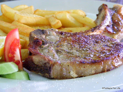 Greek cuisine - pork cutlet served with chips and salad