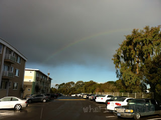 "What Mandy Thinks: Image of a rainbow over a parking lot: ""Single rainbow all the way across the sky, yeah so intense."""
