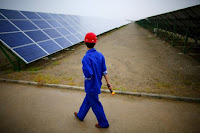 A worker inspects solar panels at a solar farm in Dunhuang, 950km (590 miles) northwest of Lanzhou, Gansu Province in this September 16, 2013 file photo. (Credit: Reuters/Carlos Barria/Files) Click to Enlarge.