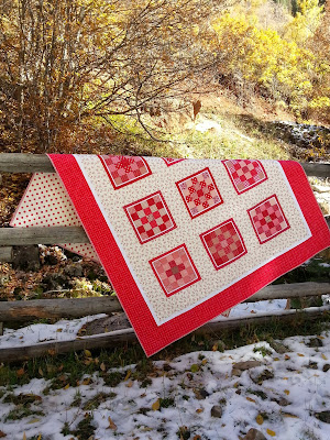 an all red quilt draped over a split log fence