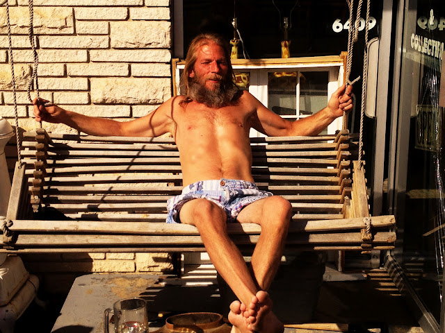 A shirtless hippie taking it easy on a porch swing a on Sunday afternoon.