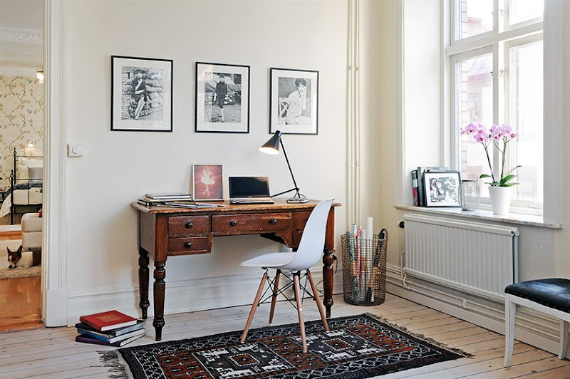 Home office in a Swedish apartment with knotty light wood floor, Eames chair, vintage desk and three framed sketches