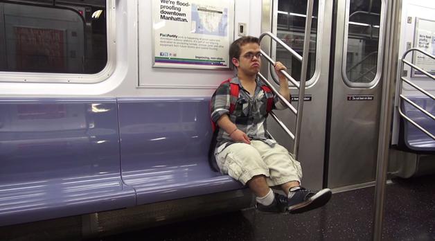 Foto de anão sentado no metrô