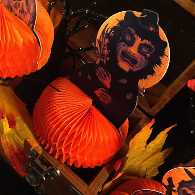 Photo of Halloween olde style paper decoration features a witch with her broom and a full honeycomb base.