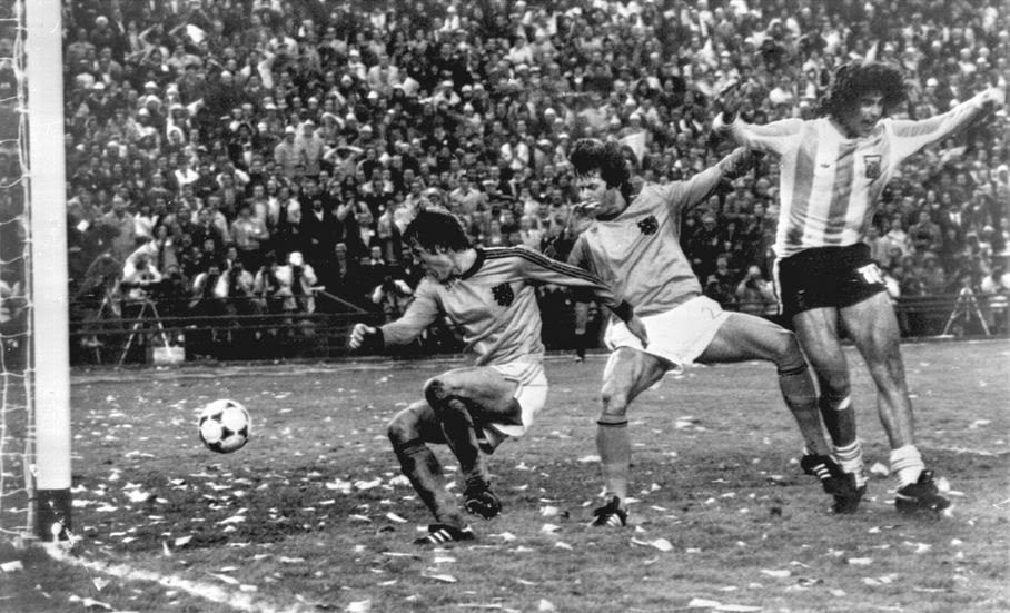 In this Sunday, June 25, 1978 file photo, Mario Kempes of Argentina, right, celebrates, after scoring Argentina's second goal against the Netherlands, during their World Cup final soccer match, at the River Plate Stadium, in Buenos Aires, Argentina. At left is Dutch player Ruud Krol, and Poortvliet at centre. On this day: Argentina wins its first World Cup in front of a confetti-laden crowd.