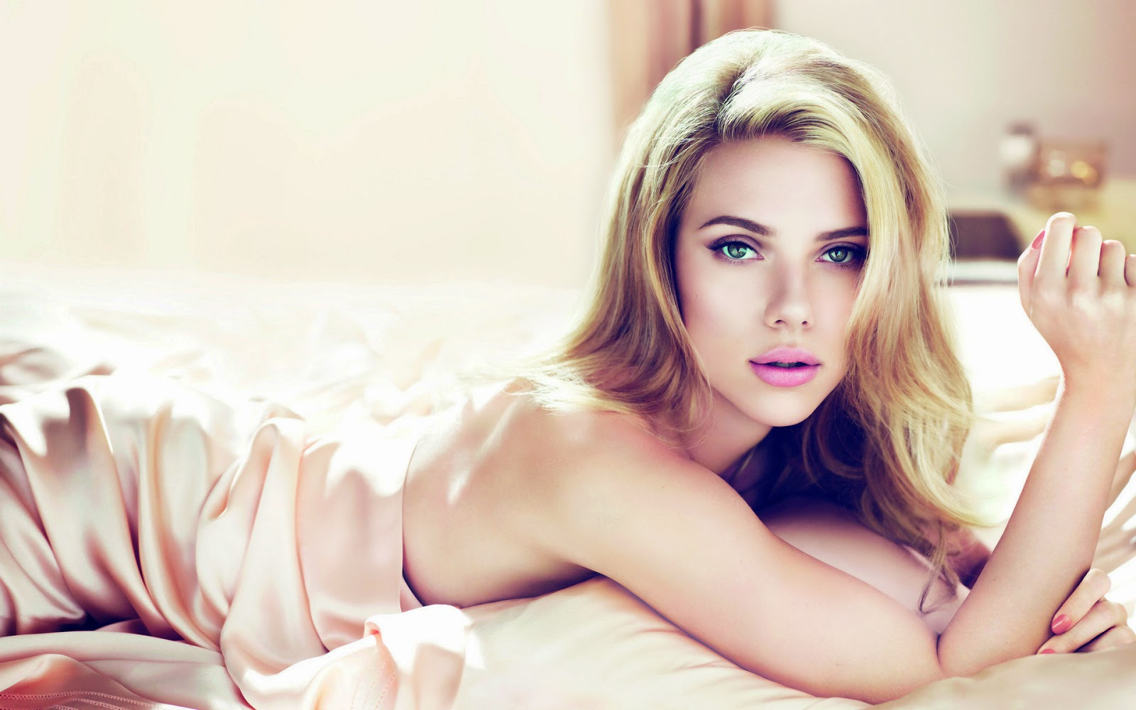 A beautiful green eyed blonde woman (scarlett johansson) lying on a bed wrapped in cream colored satin sheets