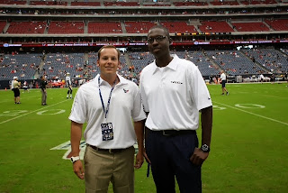 Martinez stands with Texans Security Manager Khalil Reed on the field.