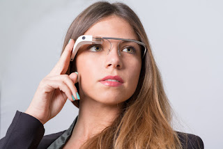 A young woman is wearing a Google Glass device