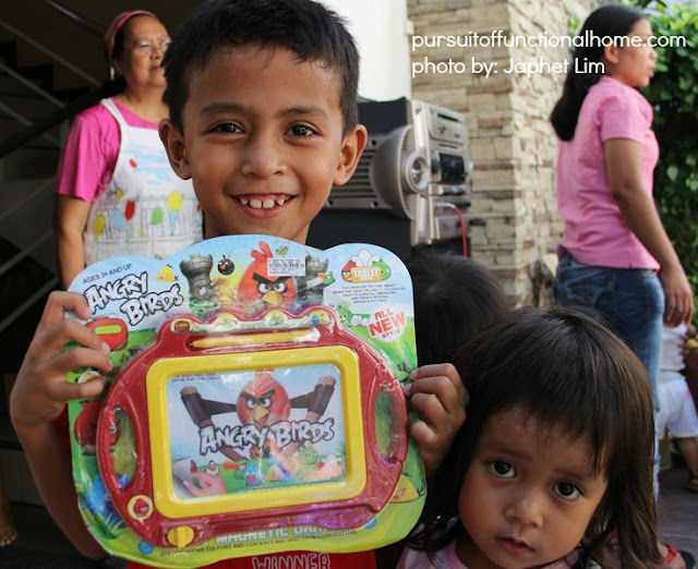 December 2012 Outreach Program. A happy face of a boy and his little sister. He is holding Angry Birds Toy.