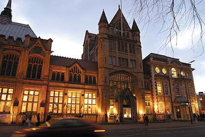 The facade of the Manchester Museum lit up from the inside at dusk.