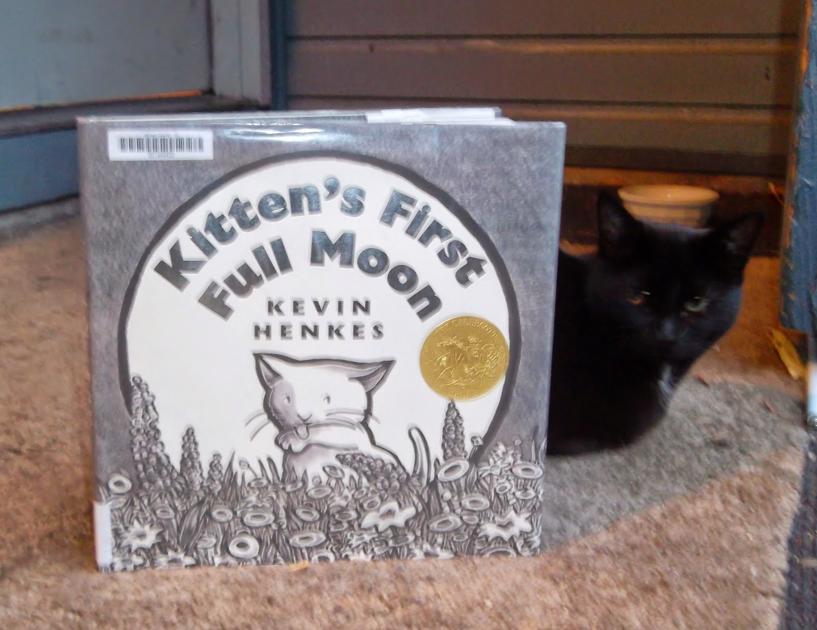 The picture book Kitten's First Full Moon by Kevin Henkes is propped up, its front cover facing forward, with my black cat Starfire sitting behind it.