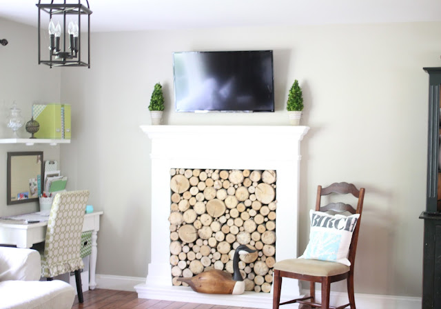 Behr Castle Path paint with faux fireplace with stacked birch wood logs and tv mounted over fireplace with preserved boxwoods www.goldenboysandme.com