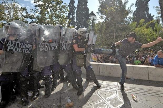 A Greek protestor kicks riot police right in the shield