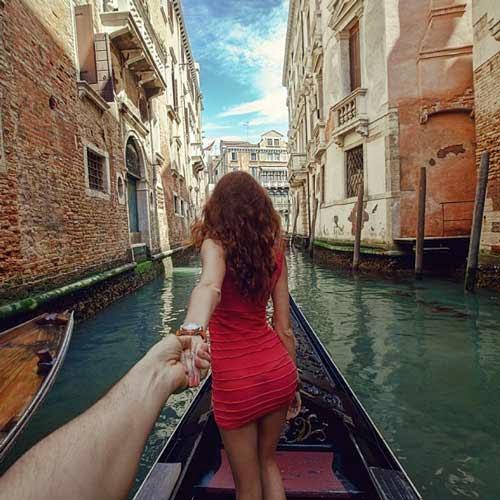 Fotografia da namorada de costas, puxando seu namorado pela mão esquerda, eles estão em uma canoa em uma das ruas alagadas de Viena, na Itália. se nota casas ou comércios em volta.
